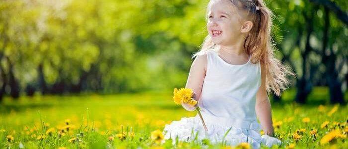Девочка играется на поле из одуванчиков